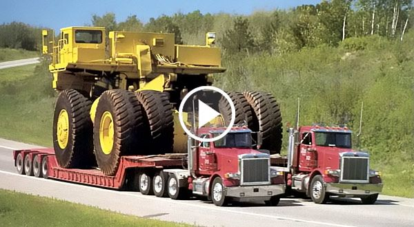 two articulated semi trucks hauling mining truck feat