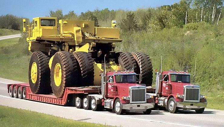 two articulated semi trucks hauling mining truck