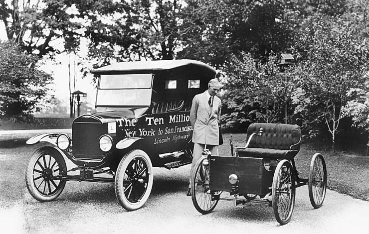 Henry Ford standing next to the first and the ten millionth Model T Ford