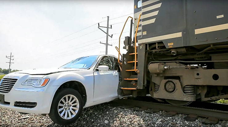 Train hits Chrysler limo stranded on tracks