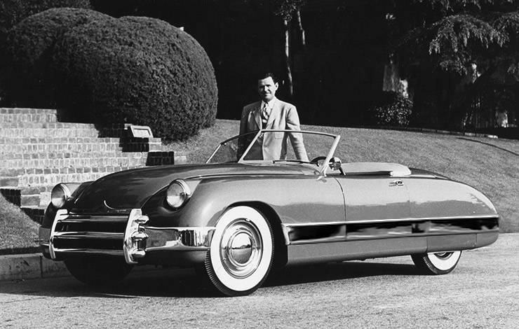 Frank Kurtis as he stands beside one of his company's convertible sports cars, 1949